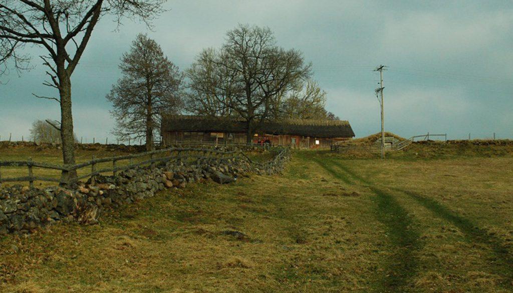 Hus på kulle med gärdsgårdar och betade marker runtomkring.