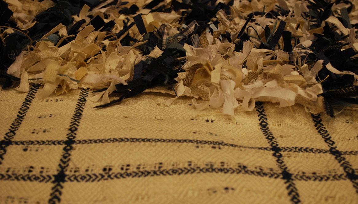 En vitt linneväv med blåa rutor, på den ligger avigsidan synlig, mockor knutna av vita och blåa trasor.