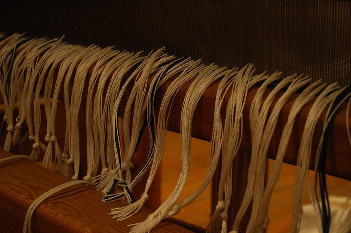 Snålframknytning, garn hänger i buntar från en vävsked med en knut längst ner.