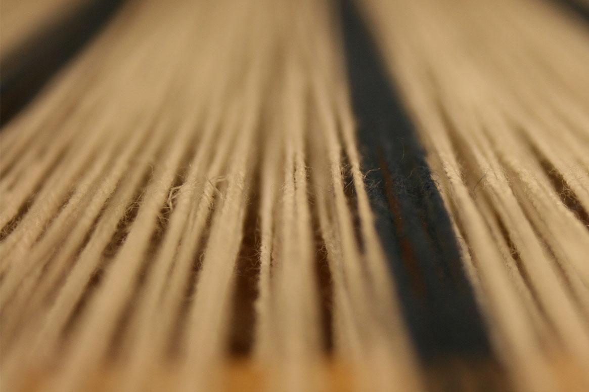 Ett gäng spända vita lintrådar med ett par blåa i en rand.
