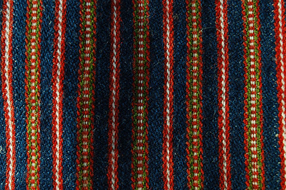 Ett randigt halvylletyg med blått som basfärg. Ränder i rött, grönt och vitt med twistränder.