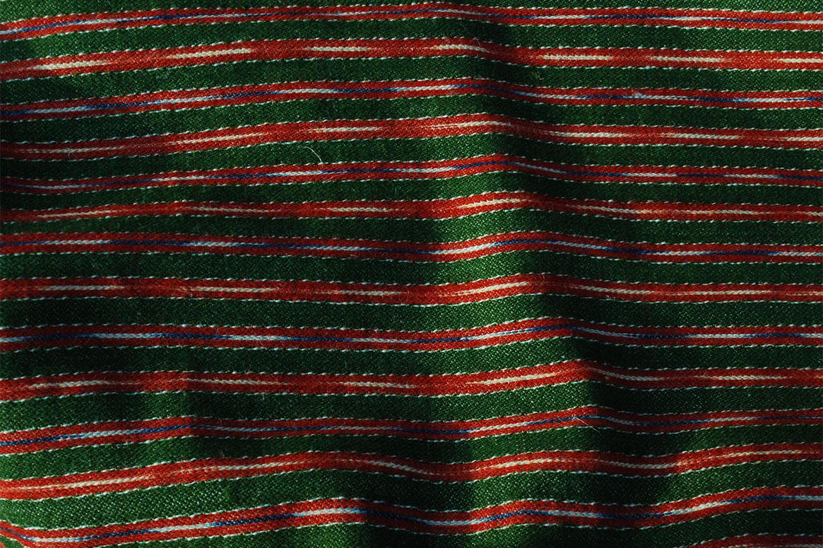 Randigt halvylle med grön basfärg och röda ränder. I de röda ränderna finns smala ränder av ikatfärgat garn i blått/vitt och rött/vitt.