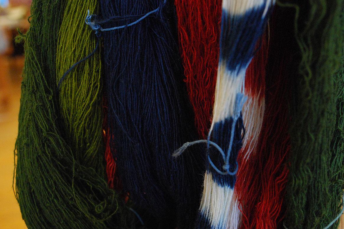 Ett gäng härvor hänger på en vävstol, alla växtfärgade i kraftiga färger av grönt, blått och rött.