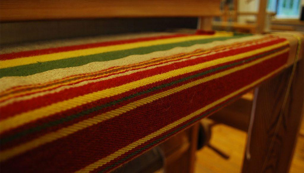 Röd-, grön-, gulrandig väv i vävstolen.