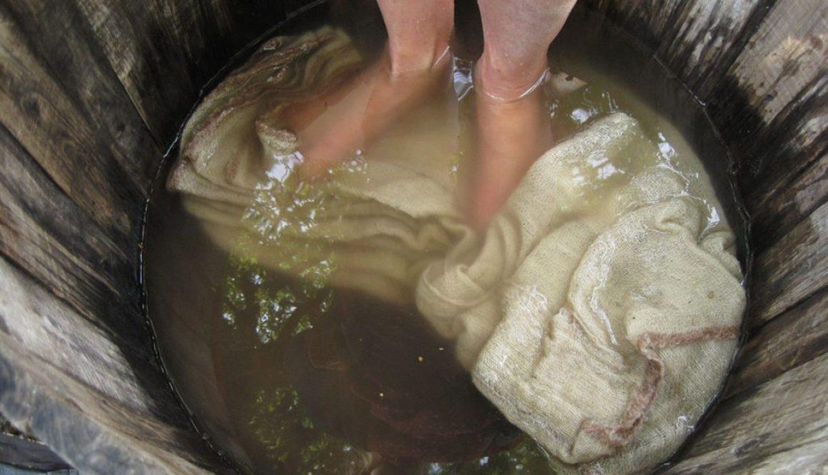 En balja med vatten där fötter stampar på ett vitt tyg.
