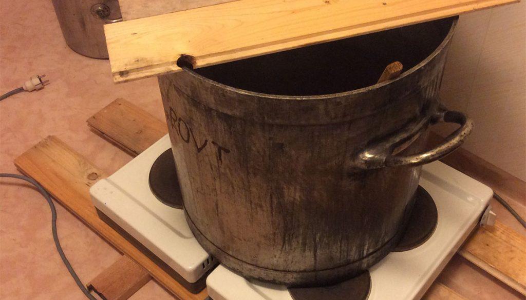 Stor gryta med brädlock på två stycken spisar. Lufttspalt uppbyggd undertill av reglar och brädor.
