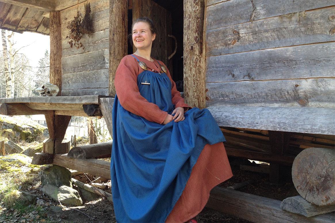 Mig i vikingadräkt framför ett timrat hus. Röd handvävd kjortel, hål hängselkjol.