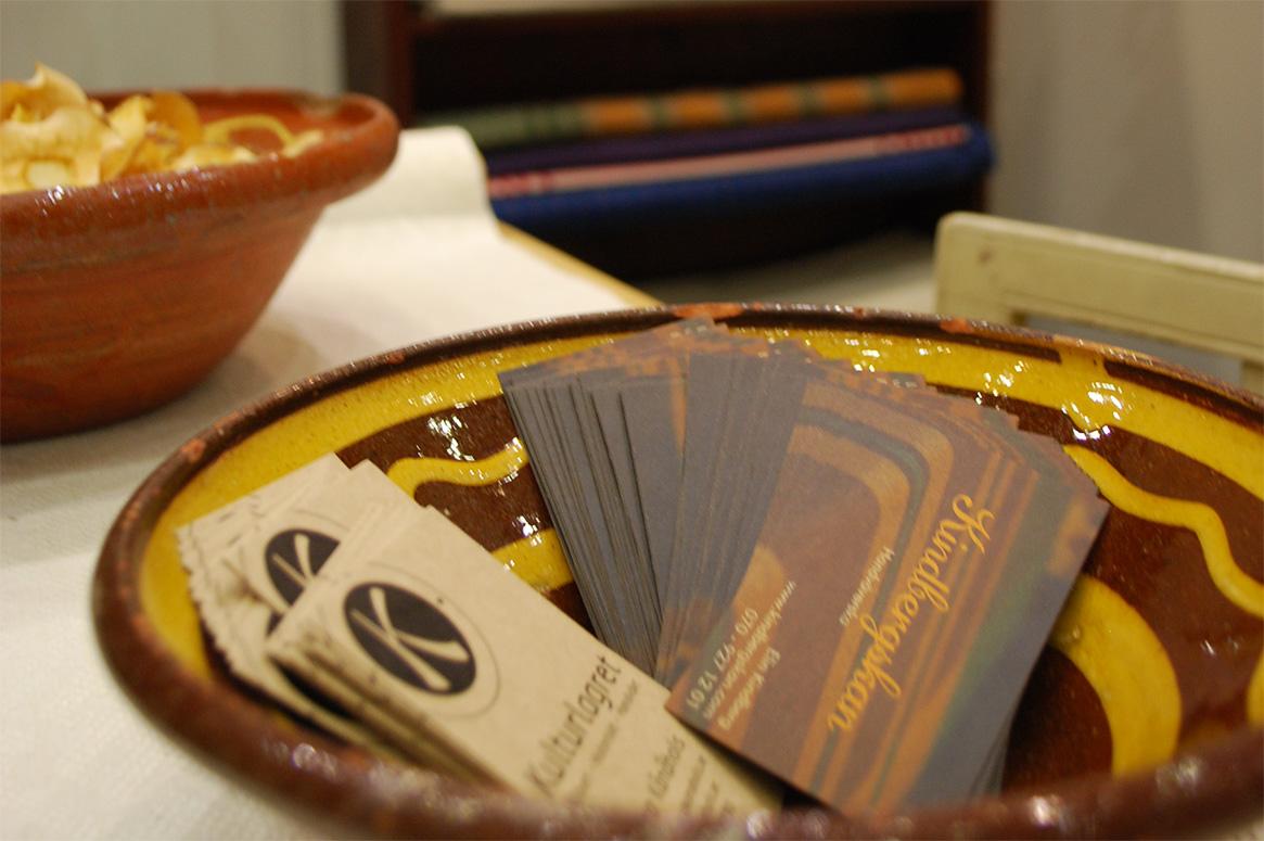 Närbild på visitkort i en keramikskål.