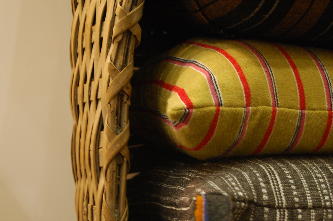 Närbild på handvävda kuddar placerade i en korg. Kuddarna är randiga, gul botten med röda ränder samt grå botten med vita ränder. Korgen hänger på väggen.